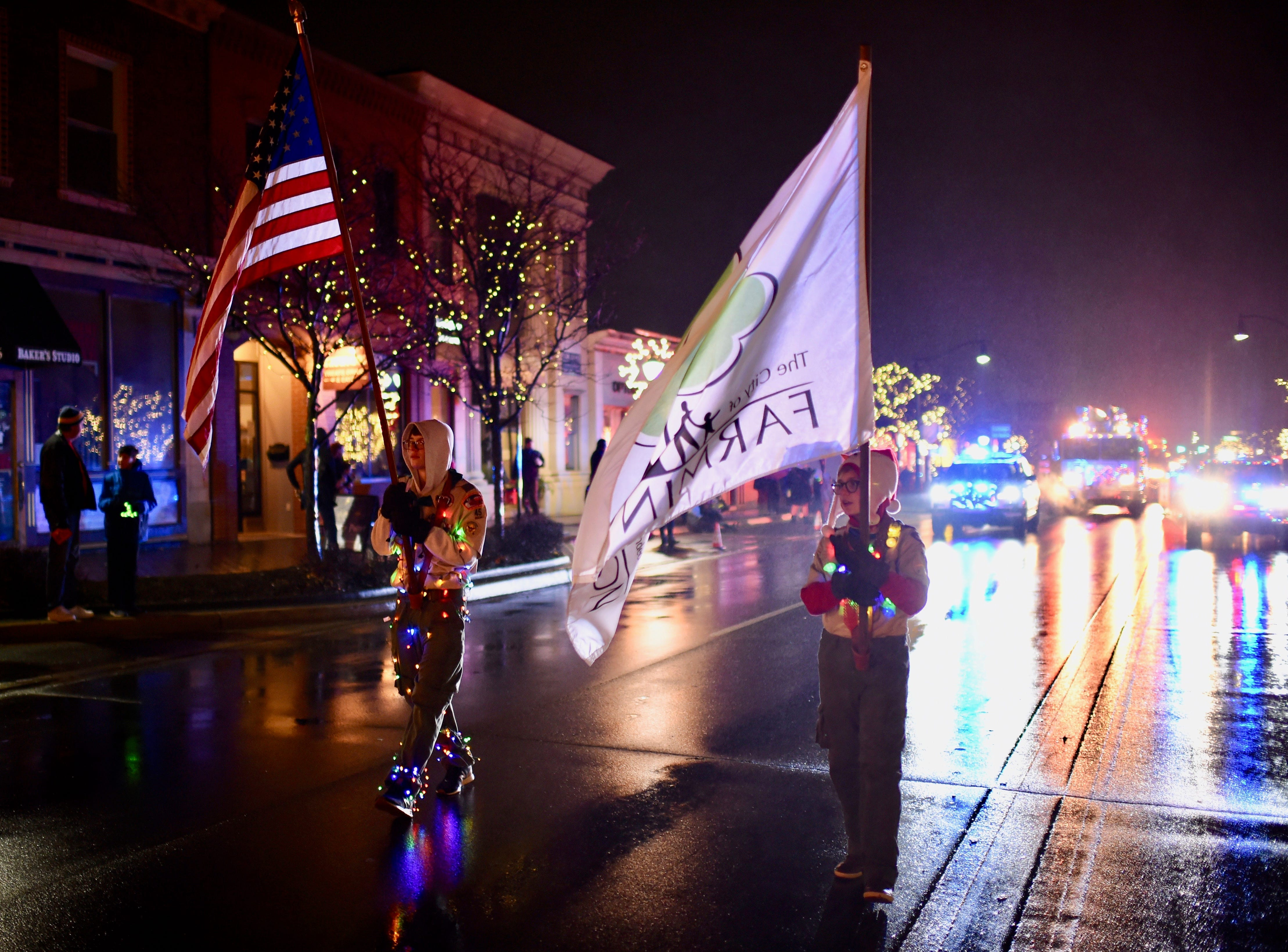 """Local Boy Scouts lead the annual """"Light Up The Grand"""" parade Saturday evening in Farmington."""