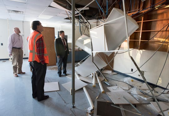 Real estate developer Ed Carson, Realtor Danny Zimmern and Escambia County School District Superintendent Malcolm Thomas inspect damage caused by vandals to the school district's former headquarters on Garden Street during a tour of the site Tuesday. Developers want to demolish the building and build a 280-unit apartment complex at the site.