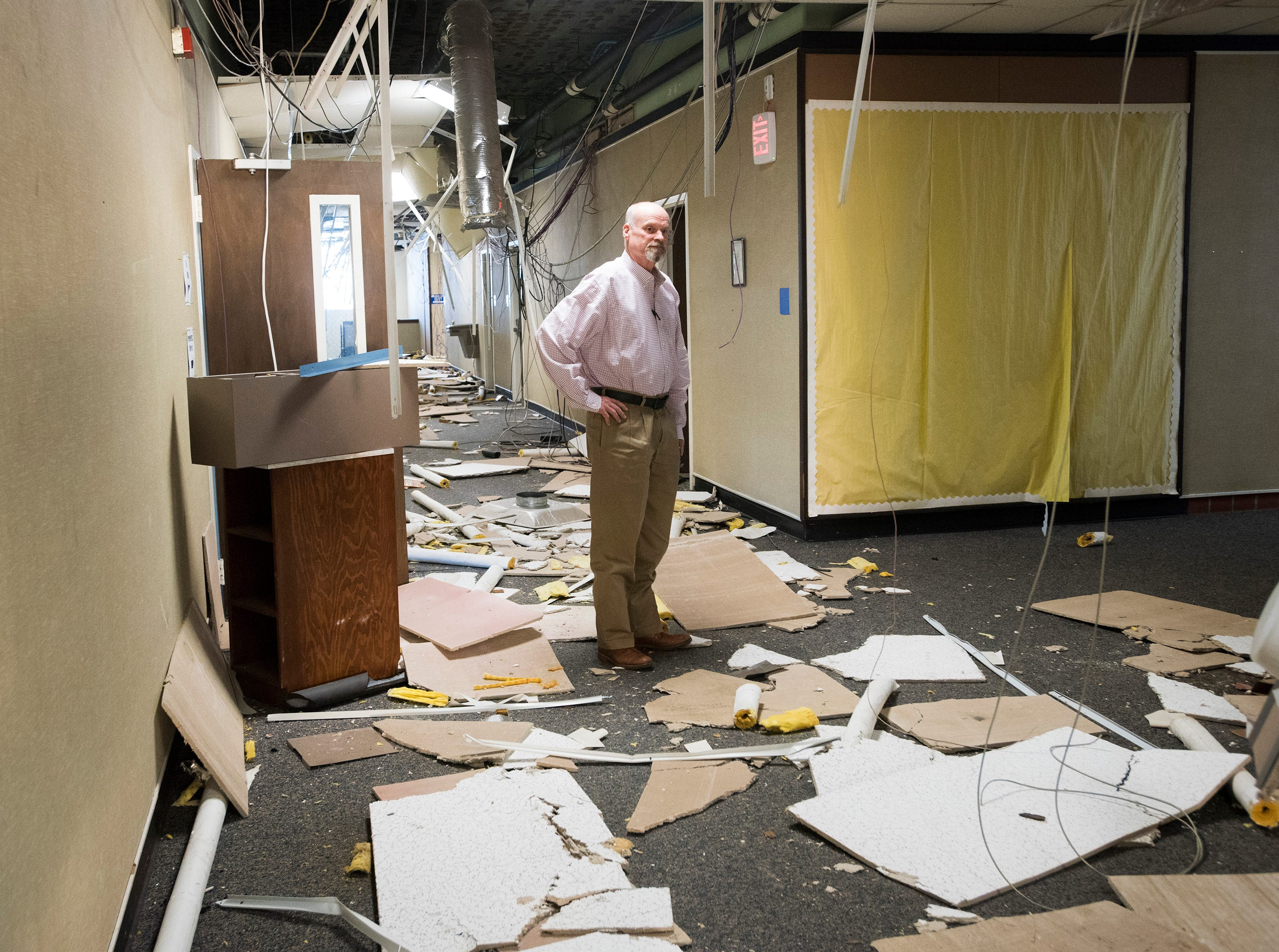 Realtor Danny Zimmern inspects the damage caused by vandals at the old district headquarters building on Garden Street on Tuesday, Dec. 4, 2018. Developers want to build a 280-unit apartment complex on the school district site.