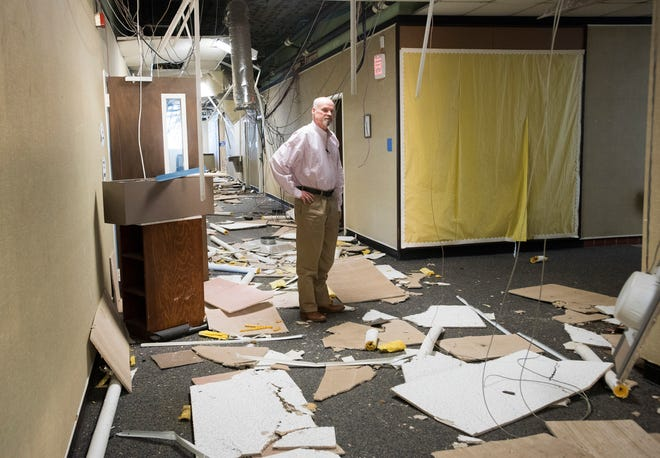 Realtor Danny Zimmern looks Tuesday at damage caused by vandals at the former Escambia County School District headquarters on Garden Street in downtown Pensacola. Developers are asking for approval to demolish the building and build a 280-unit apartment complex at the site.