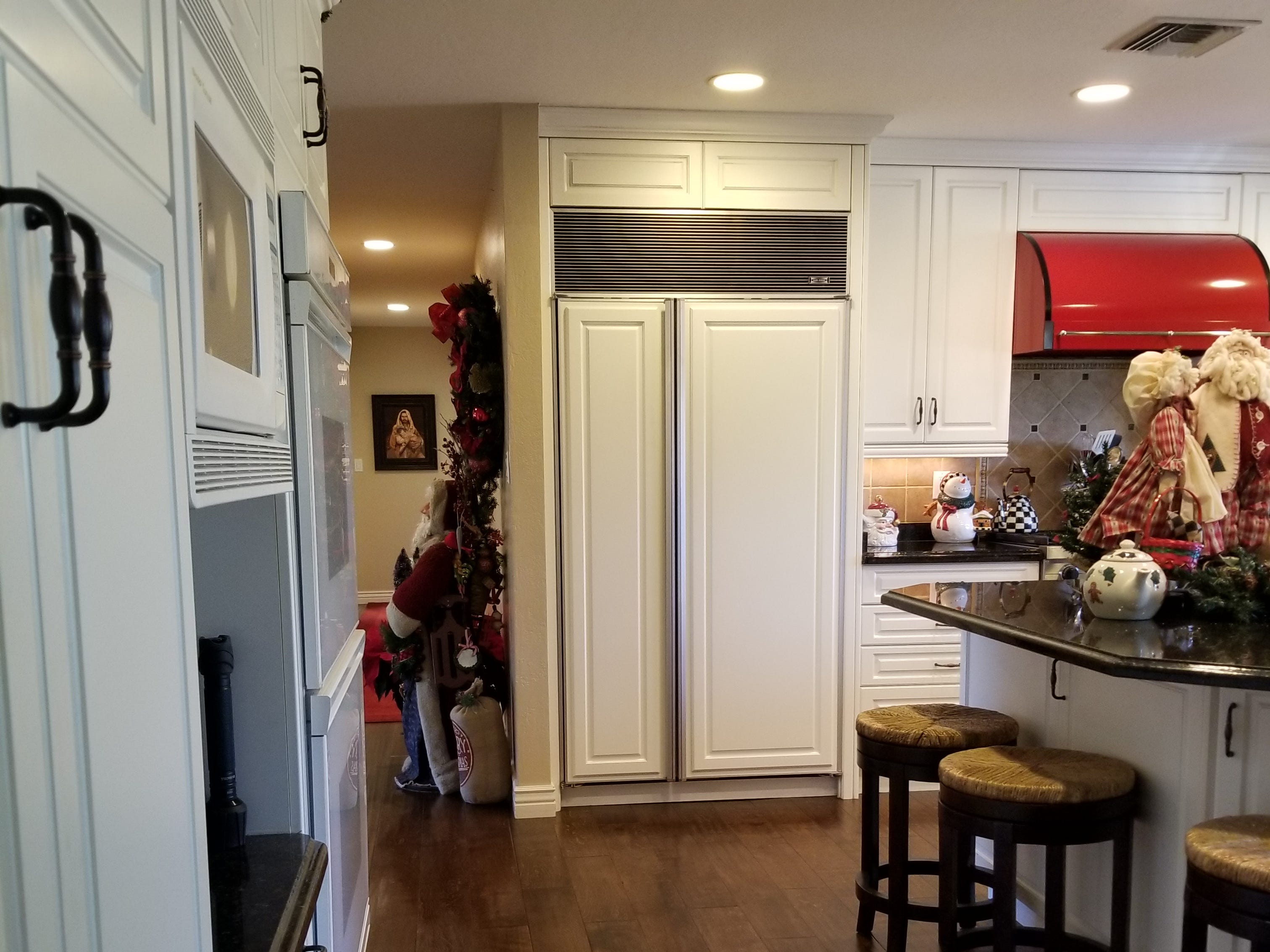 The kitchen underwent an extensive remodel in 2009. Dark wood cabinets were replaced with stunning white; a soffit of cabinets over a peninsula was removed, allowing for an open sight-line and access to the sunken family room. Ceilings were raised and abundant recessed lighting and new flooring added. Double ovens, a gas grill and Sub-Zero refrigerator with matching panels and fire-red stove vent are Bob's favored kitchen features. A later revision enlarged the island, providing additional seating for five, and engineered floors in dark woods match the newly upgraded hallway to the foyer and bedroom suite to achieve consistency throughout. Double French doors provide access to an oversize patio, lush backyard and pool area. It is stunning in every detail, and is reflective of Linda's farm-influenced childhood in Duncan and Laveen.