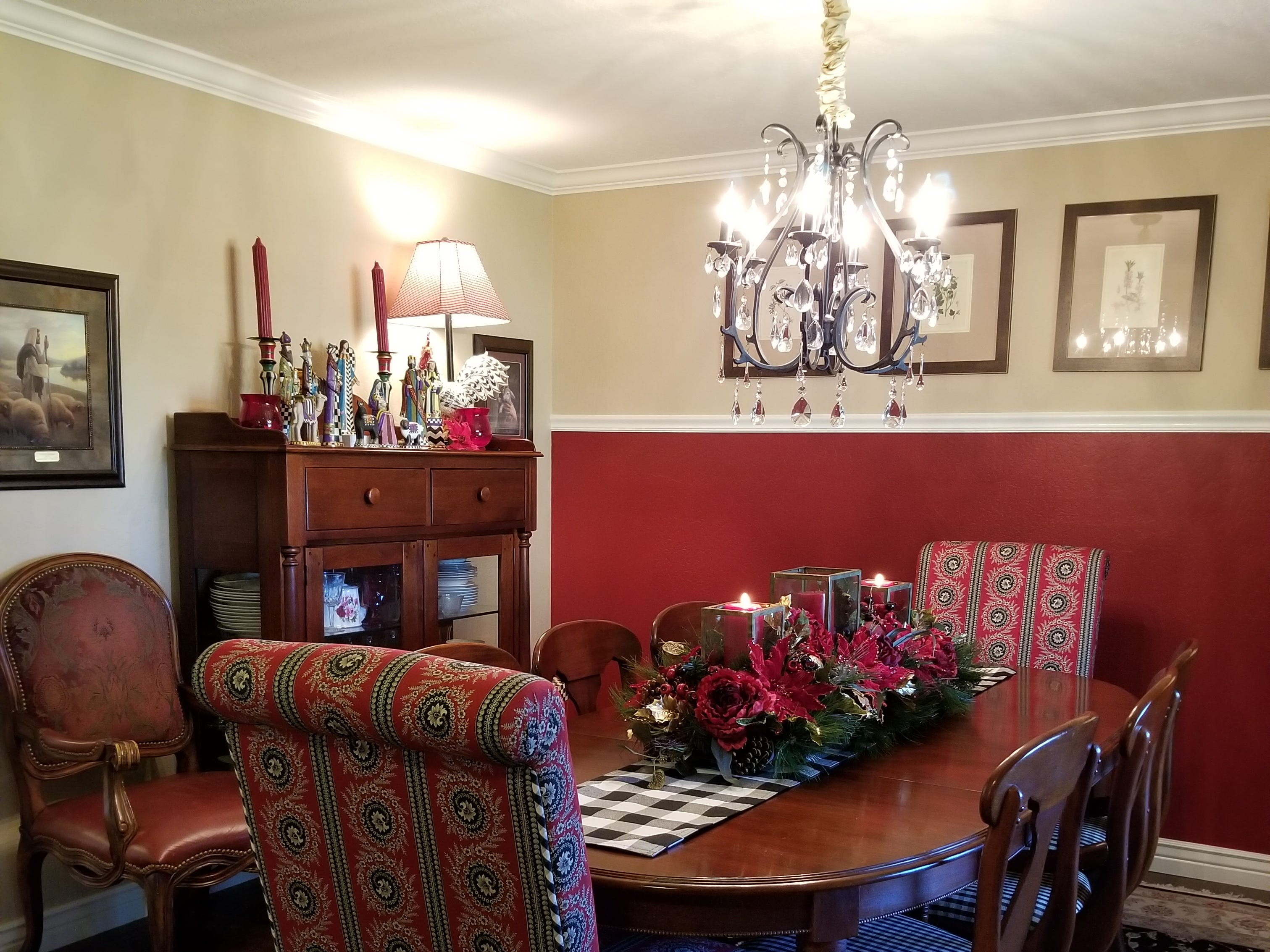 The sunken dining room sits to right of entry. Rich in design, it features exquisite draperies and sheers frame the oversize window and views of the front porch. Two upholstered chairs anchor the large table at opposite ends; the remaining seating for eight sports black and white checkered seats on wooden frames. Crown moldings and a crystal chandelier complete the scene, with a Turkish area rug purchased during travels there completing the formal yet inviting dining room. A black and white checkered table runner pulls from the kitchen décor.