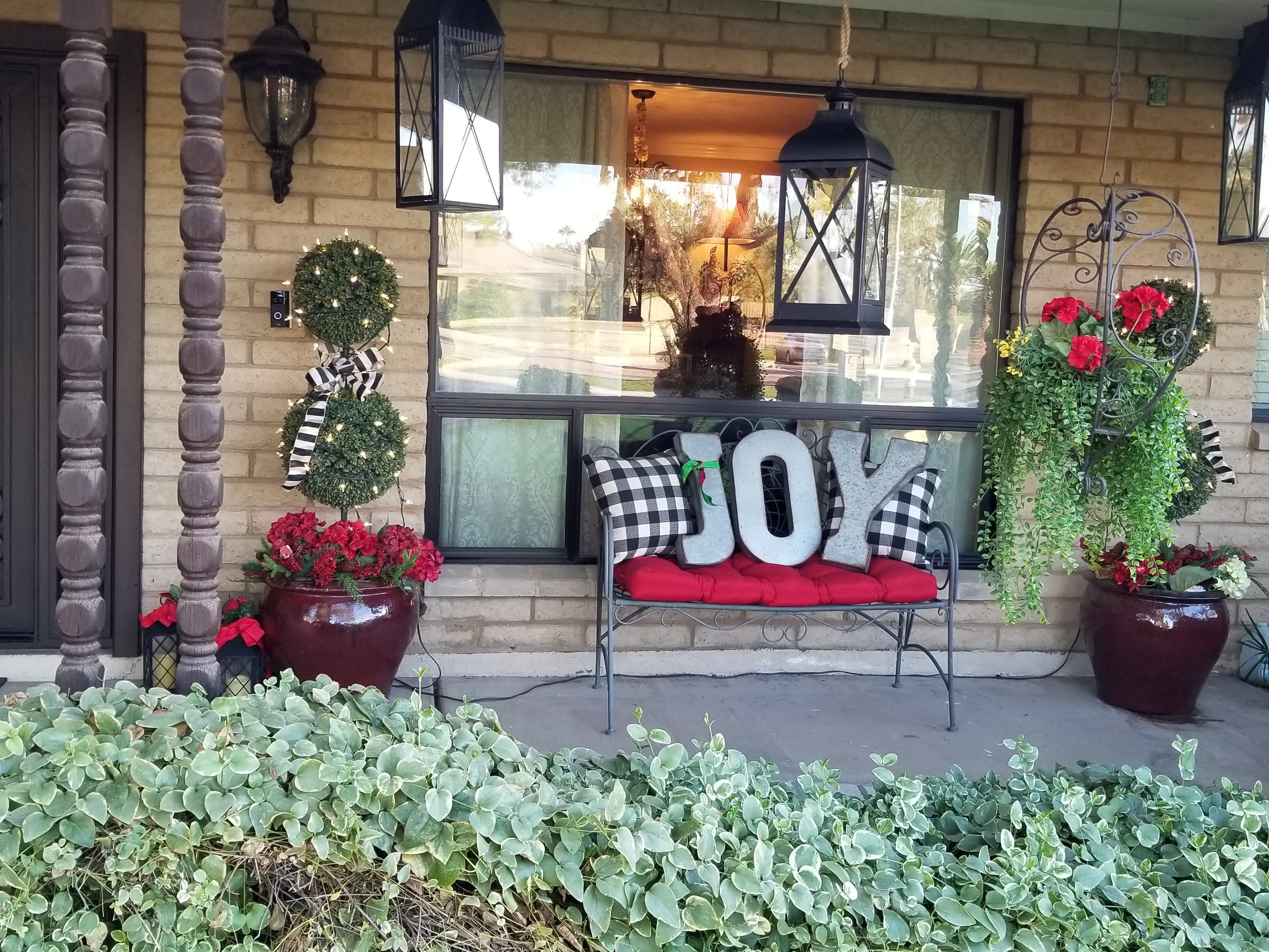 Leaving no stone unturned for the holidays, the Lees' front porch is dressed to the nines. An oversize stuffed moose in his Christmas glad rags, an iron bench announcing JOY amid black and white checkered pillows, and a collections of lanterns greet visitors to the warmth of the Lees' hospitality.