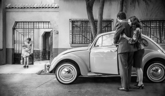 "In ""Roma,"" Cleo (Yalitza Aparicio) and her young charge (Marco Graf) are watched by Antonio (Fernando Grediaga) and Sofia (Marina de Tavira)."