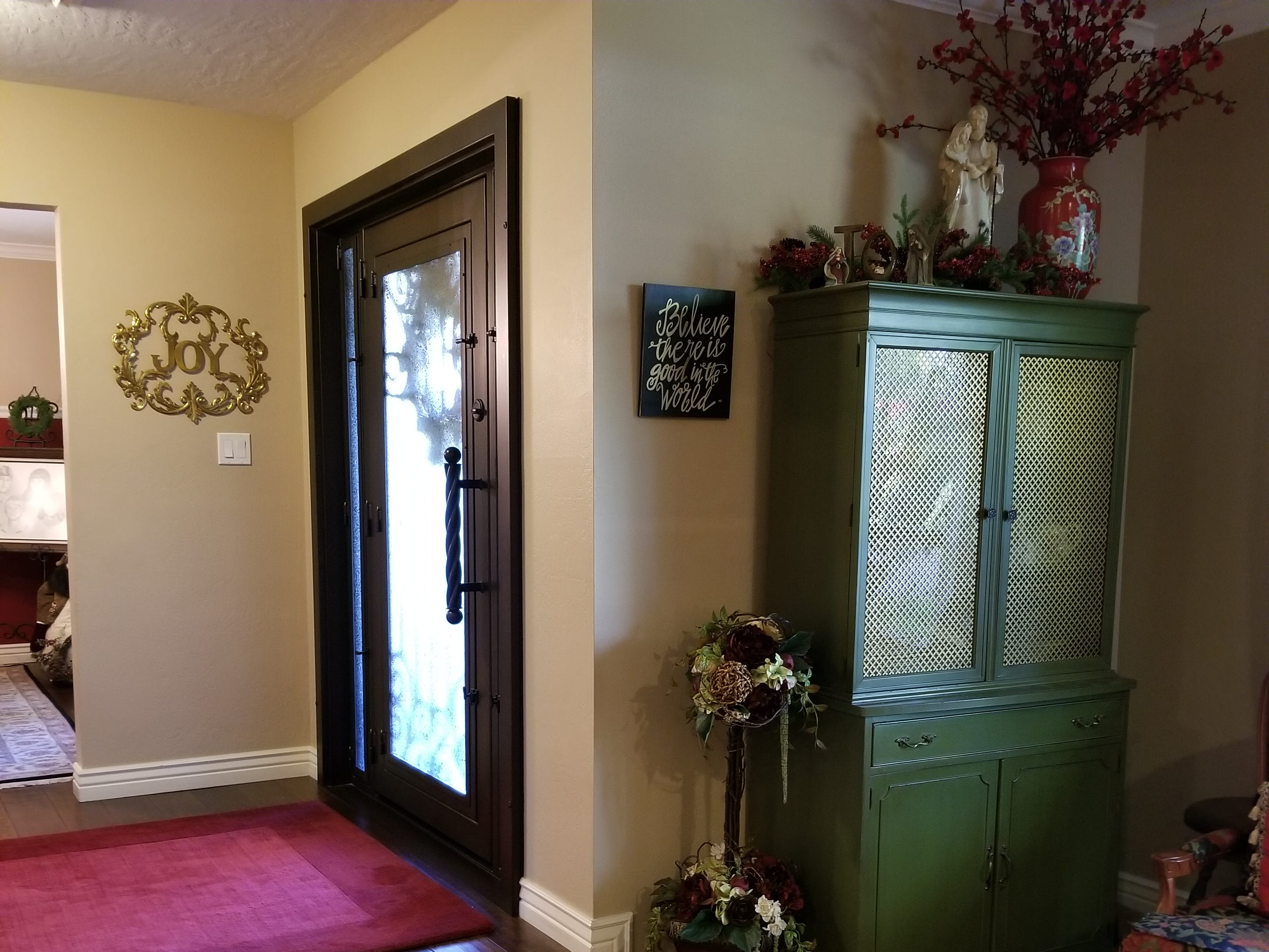 A raised entry of engineered dark wood flooring separates the living room to the left, and formal dining room to the right. Double French doors were a thoughtful design element during the years of raising their family, keeping the two formal rooms intact. An antique sewing cabinet holds court just before the French door entry into a hallway leading to bedrooms on the left, and kitchen, den and office to the right.