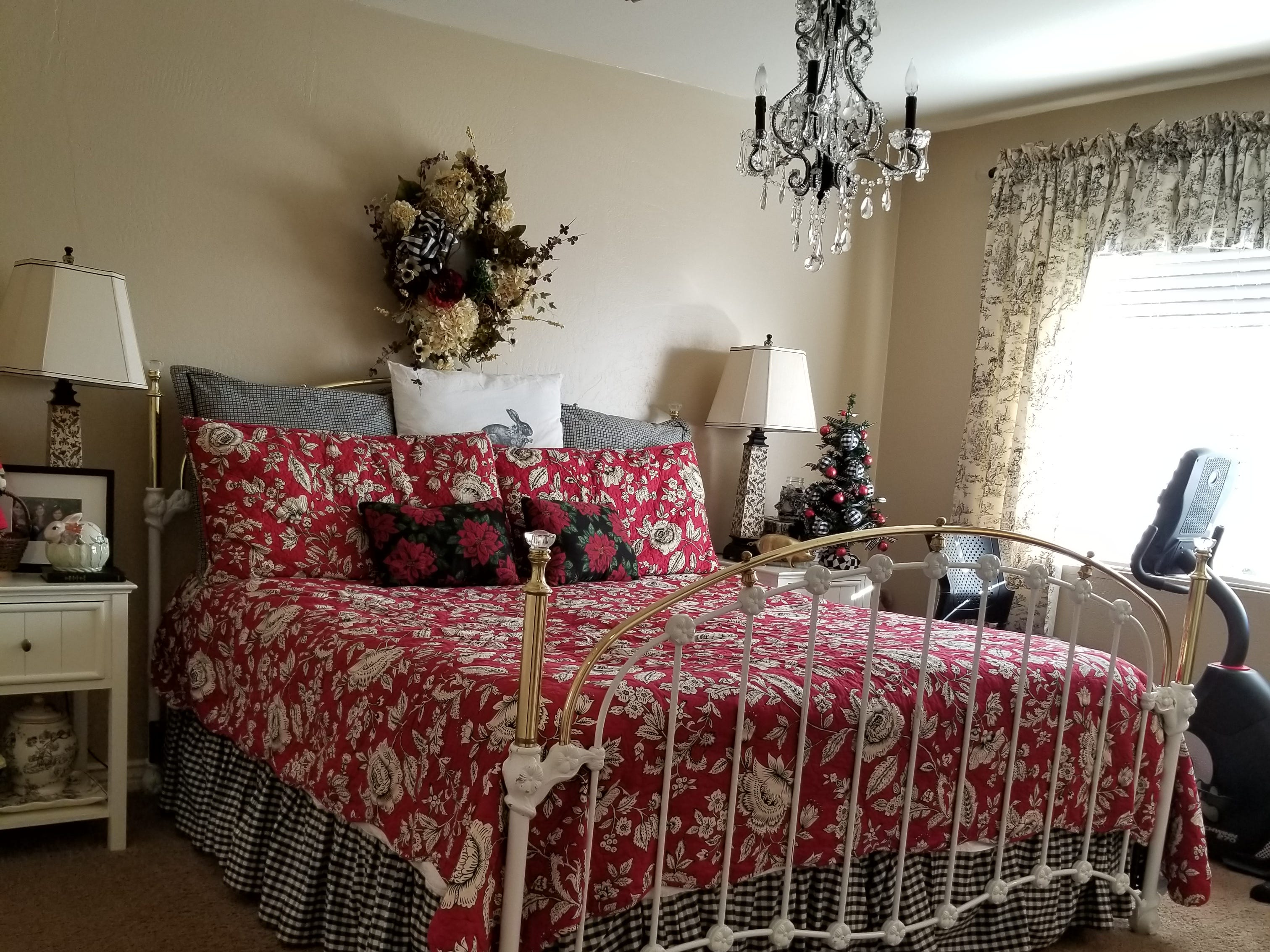 The second guest room is complete with delightfully dressed layers of fabrics on an iron bed, a crystal chandelier, and black and white with red influence throughout.  Each bedroom features walk-in closets. An elegant Queen Anne chair and floor lamp shade in a corner is upholstered in fabric matching the bedroom drapery.