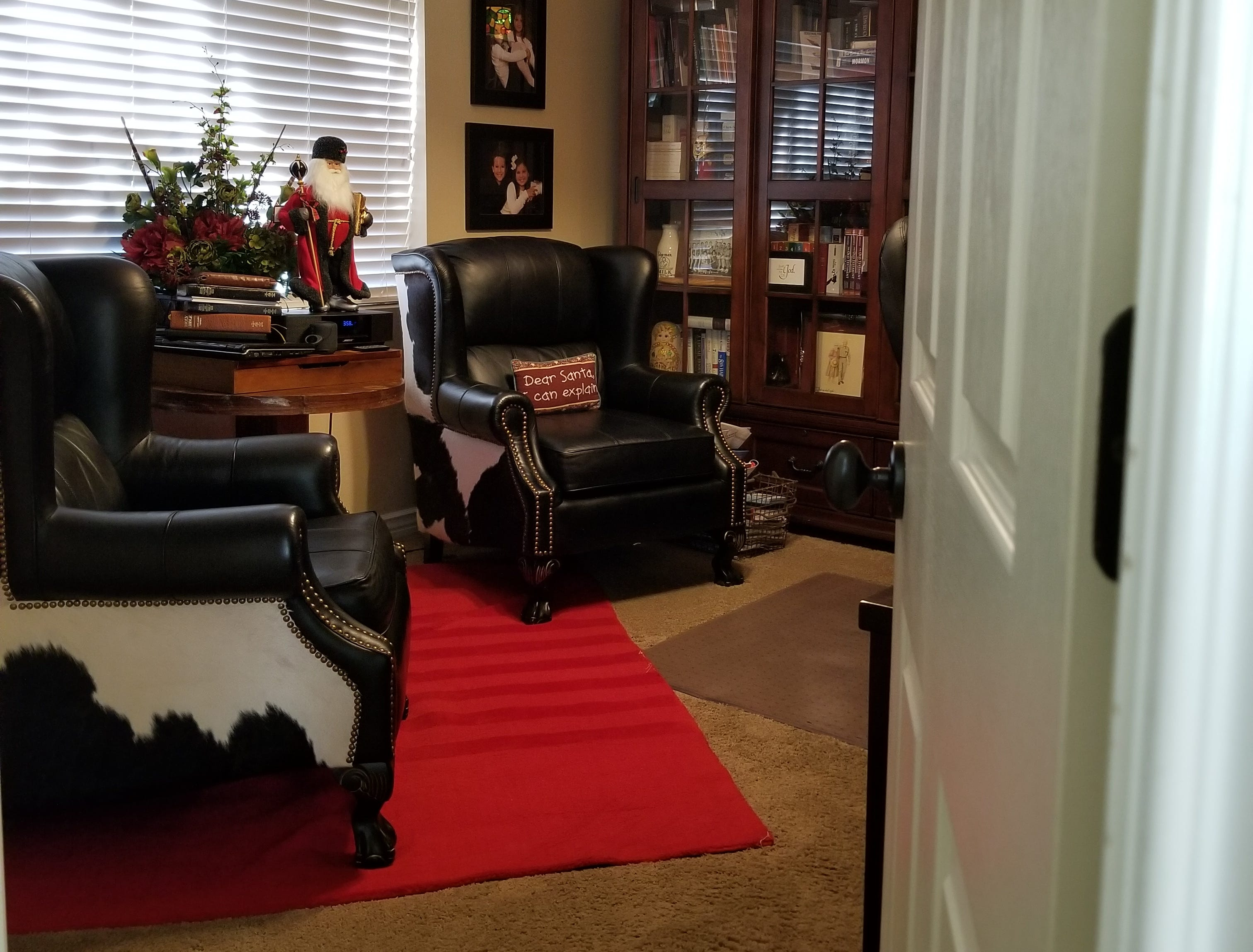 """The fourth bedroom suite was converted to an office as the Lee children flew the nest. It is anchored by two large leather wingback chairs sporting Holstein hides.  A Tiffany chandelier, bookcase and large desk complete the room. """"Dear Santa, I can explain"""" and """"Can I show you the right way to do that?"""" signage reflects the playful personality of the family.  A full-size bathroom completes the west end of the home."""