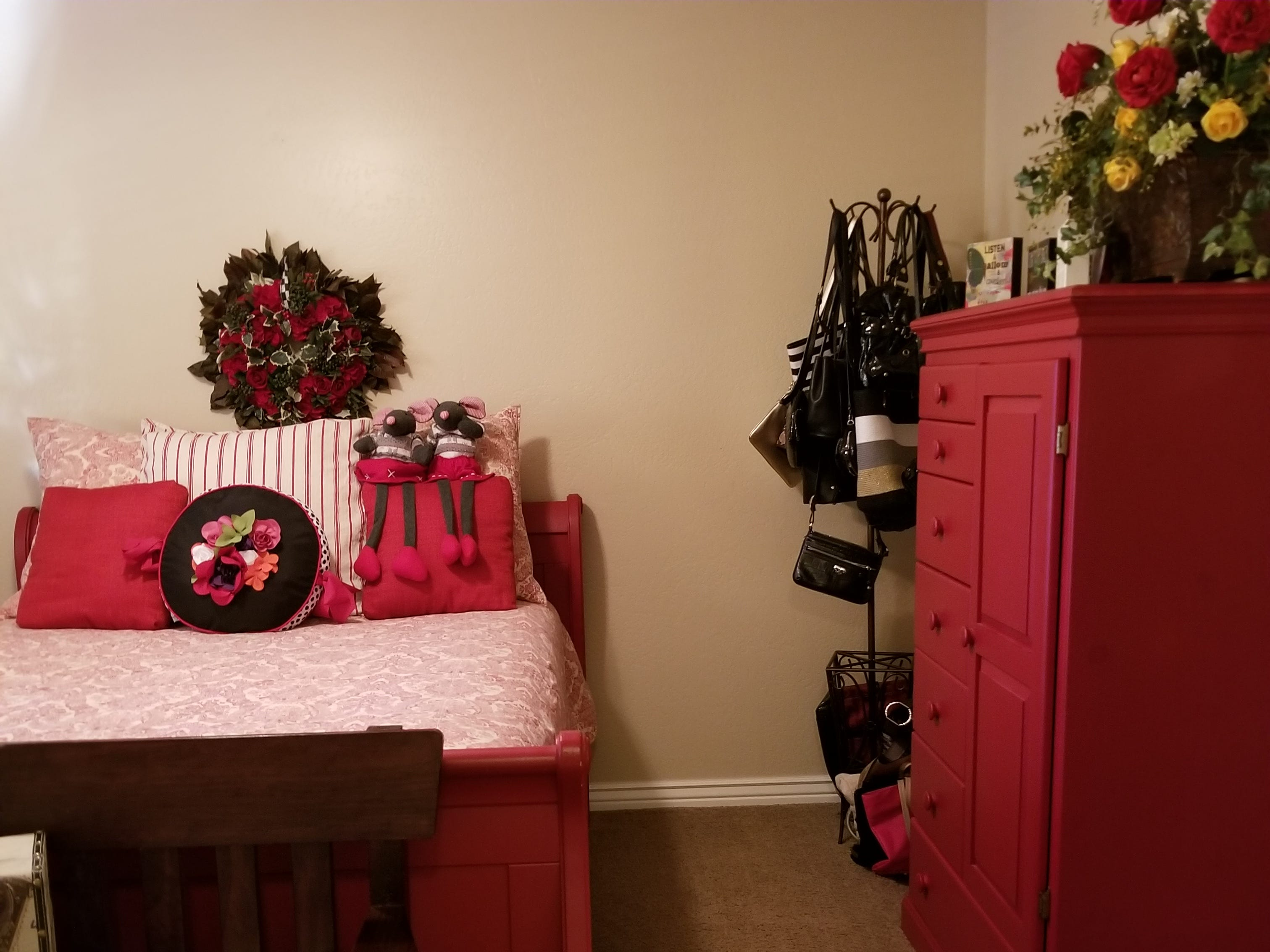 """A signature sleigh bed and chest painted bright red are center point in the first guest room, joined by a """"Jack and Jill"""" bathroom to an opposite bedroom. A touch of Christmas prevails in the bathroom as a holiday rug complements the floor tile and dark vanity."""