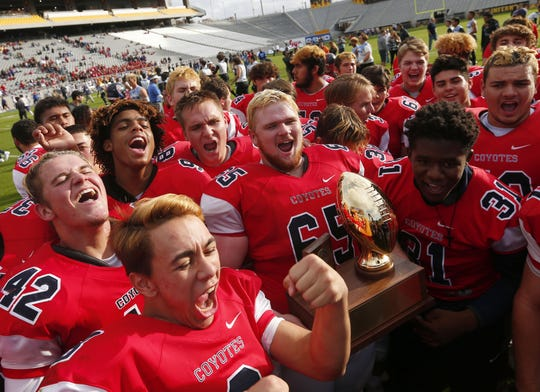 Centennial players celebrate after winning the 5A state championship on Saturday.