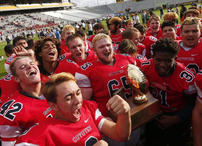 Centennial players celebrate after winning the 5A state championship.