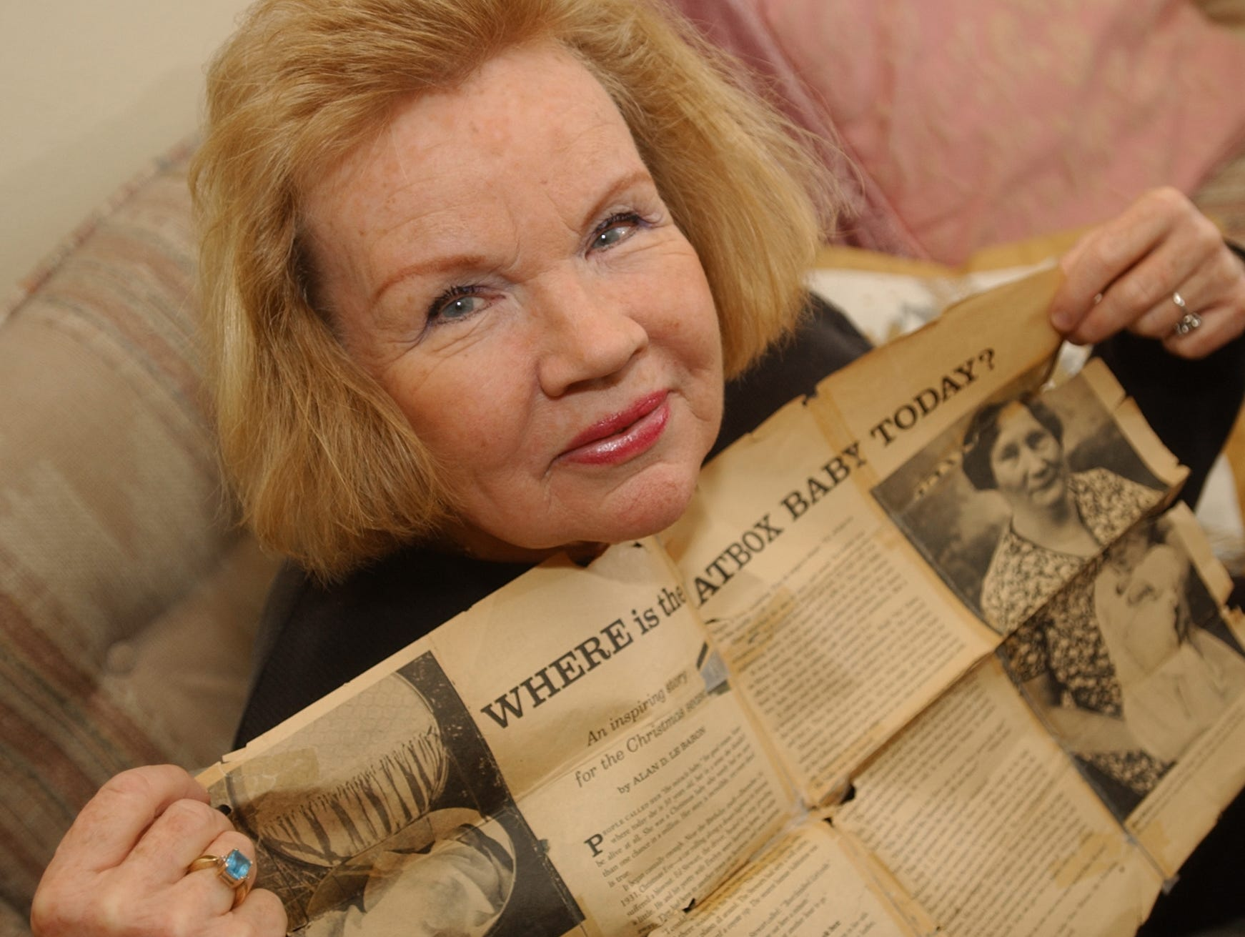 Sharon Elliott, shown in a 2003 file photo with a clipping about herself from a 1951 Parade Magazine.  As a newborn, she was left in a hat box in the desert near Superior.