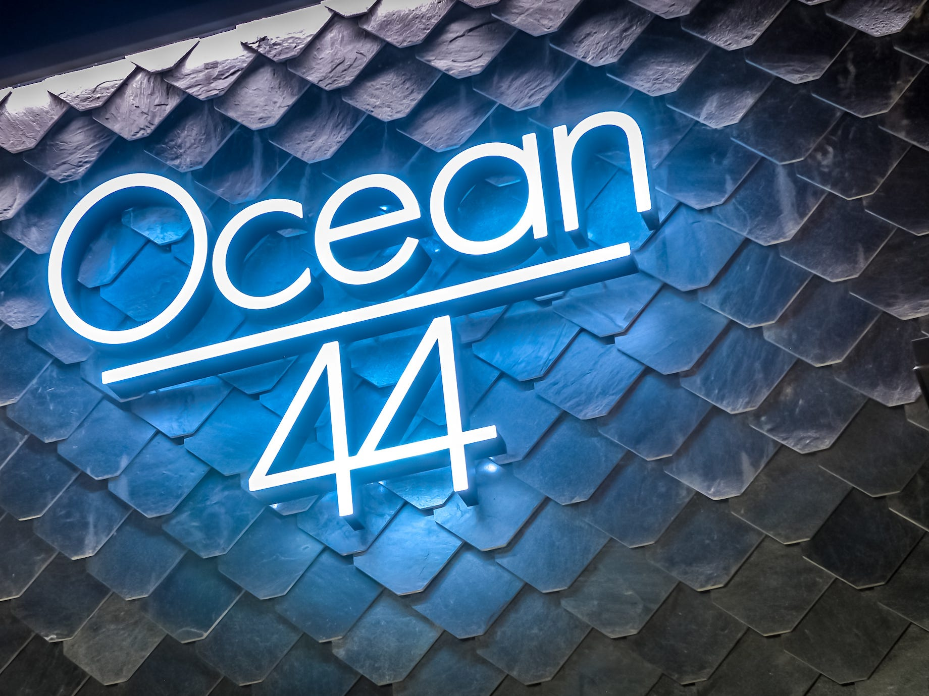 Ocean 44 signage illuminates the tiles that are made to look fish scale tiles.
