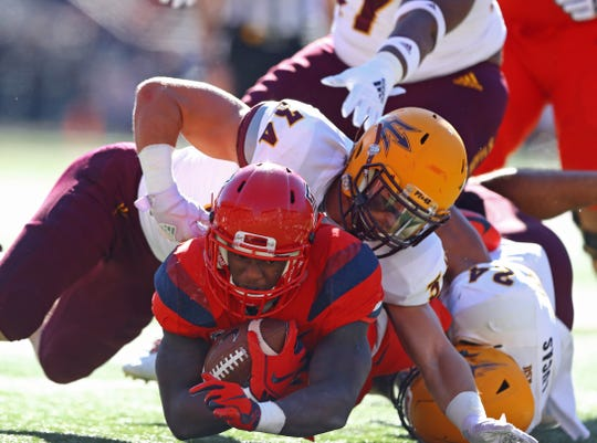 Arizona Wildcats running back J.J. Taylor (bottom) is tackled by Arizona State Sun Devils linebacker Kyle Soelle (34) in the first half during the Territorial Cup at Arizona Stadium.