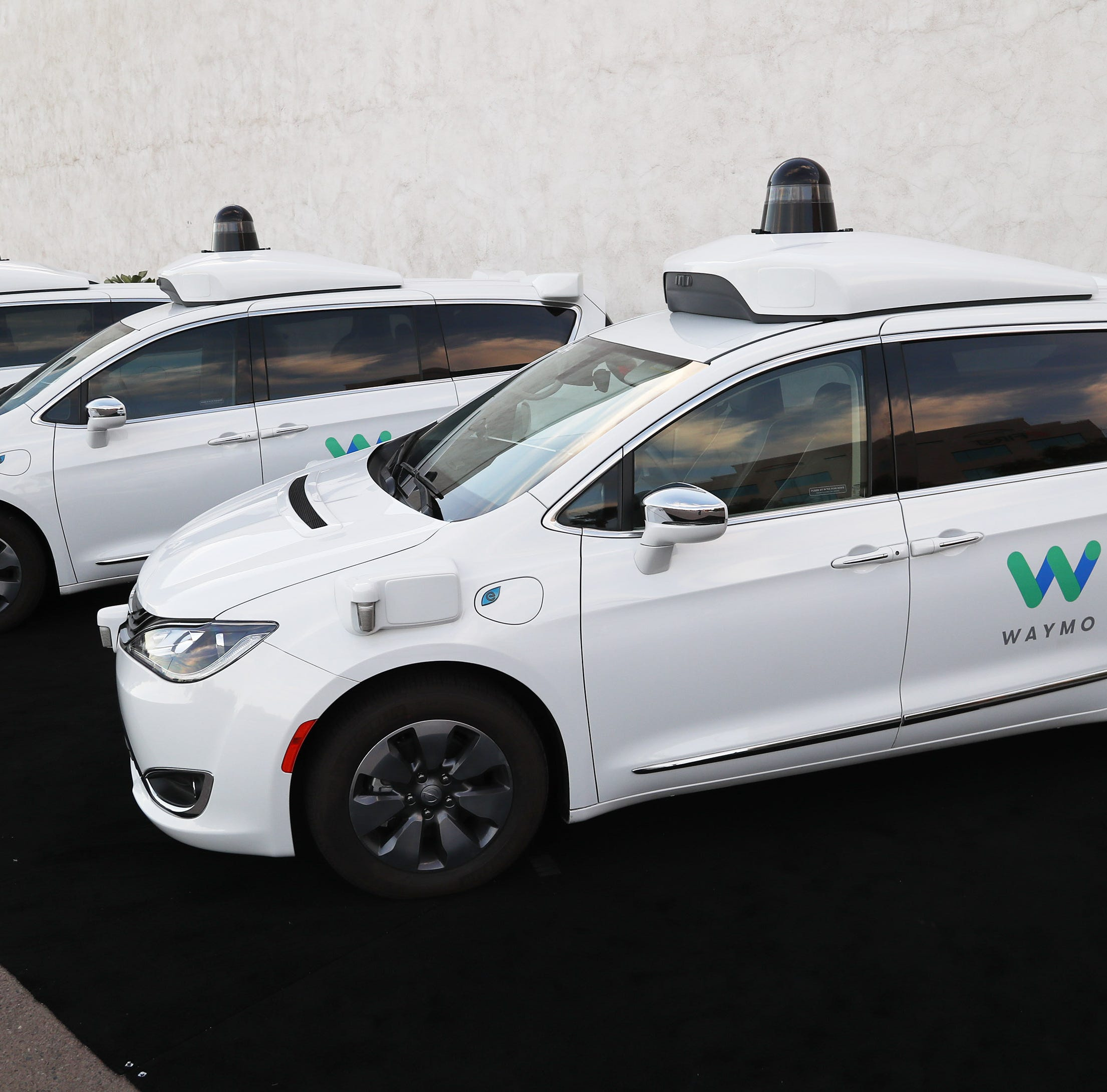 Waymo self-driving cars are seen Nov. 28, 2018,...