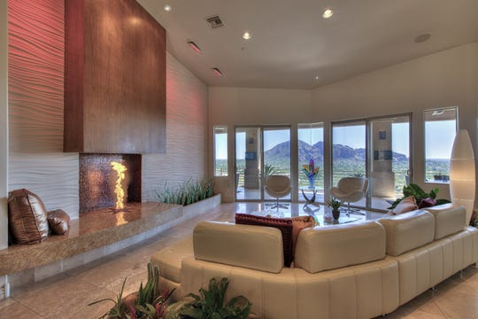 This Paradise Valley home features  walls of glass that provide stunning views of Camelback and Mummy Mountain.