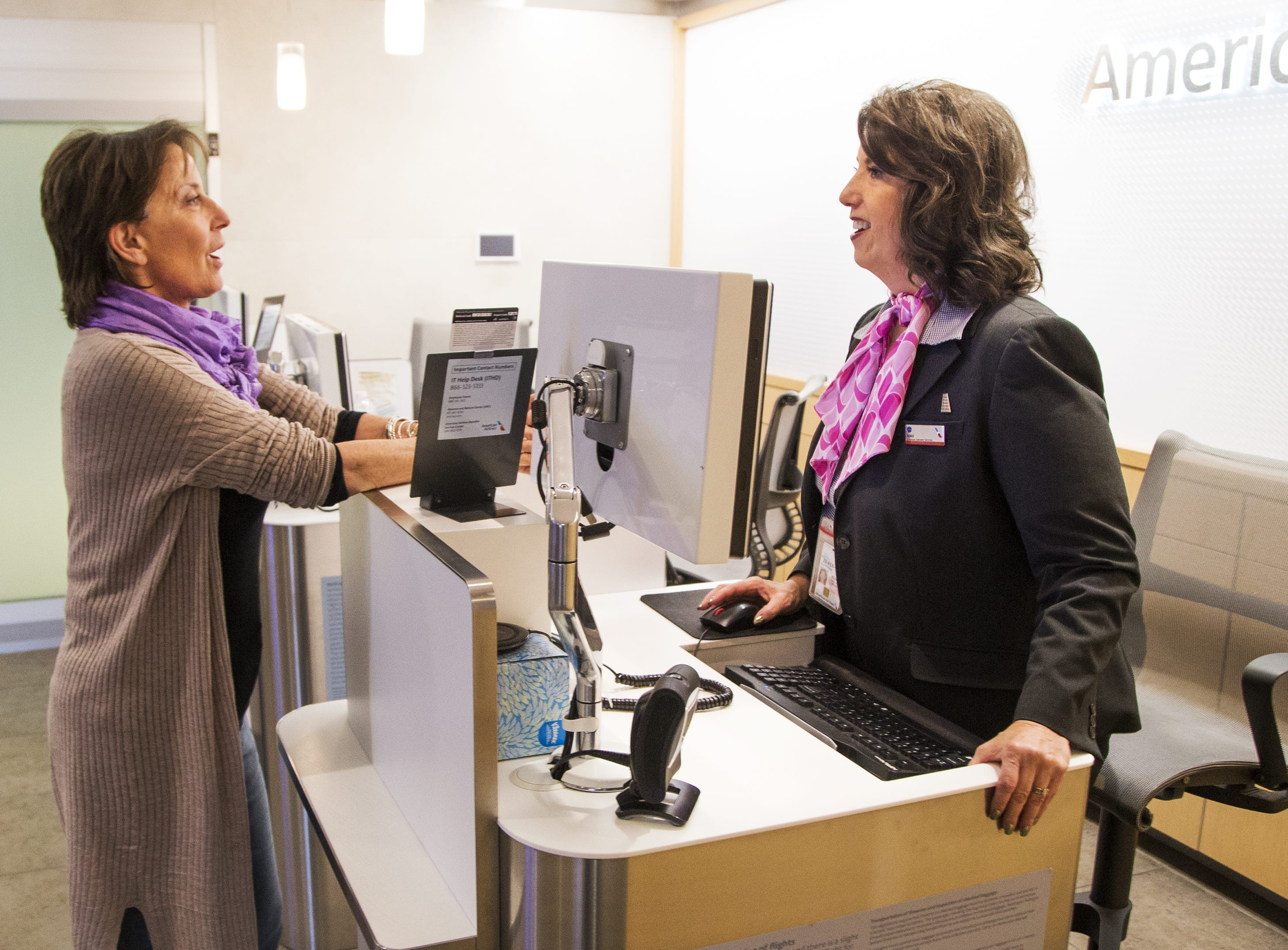 Customer Monica King of Morro Bay, California, asks premium service customer representative Renee Seavey, right, a question at check-in desk of the American Airlines Admirals Club in Terminal 4 at Sky Harbor International Airport, Wednesday, October 31, 2018.
