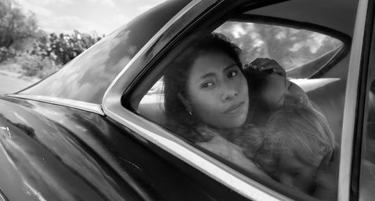 "Cleo (Yalitza Aparicio) comforts Pepe (Marco Graf) and Sofi (Daniela Demesa) in ""Roma."""