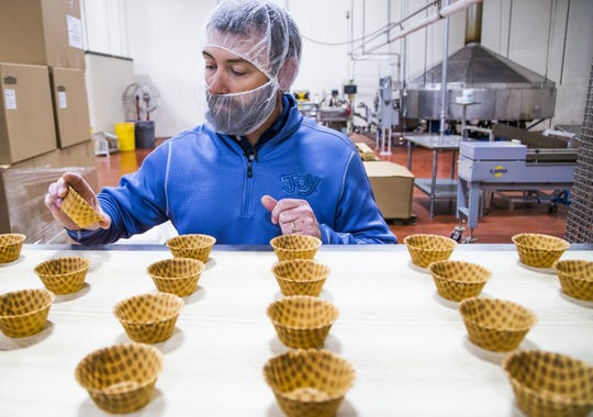 Joy Cone Company general manager Joe Pozar, Jr.,checks out waffle cups as they move down the conveyor belt at the Joy Cone Company plant in Flagstaff, Wednesday, November 29, 2018.