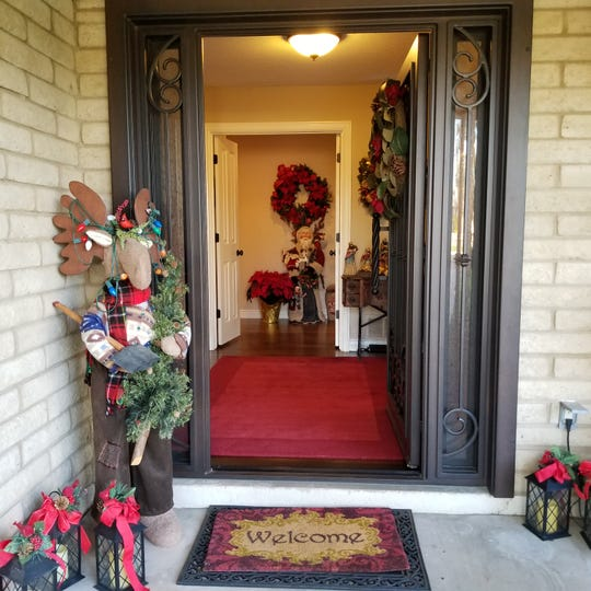 The front door is a beautifully designed custom glass and iron security entry door, allowing natural light to be diffused throughout the entry while providing eye candy for passers-by. The oversize elongated door handle adds additional interest.