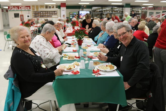Bev Dowling, left, and Jack Reindel, right, enjoy their meal at the annual B-C-S Senior Citizen Christmas Luncheon at Oak Harbor High School on Tuesday.