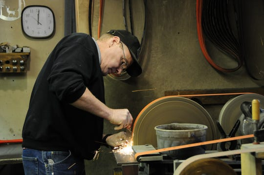 Knifemaker Michael Morris grinds a blade at his shop in Yale.