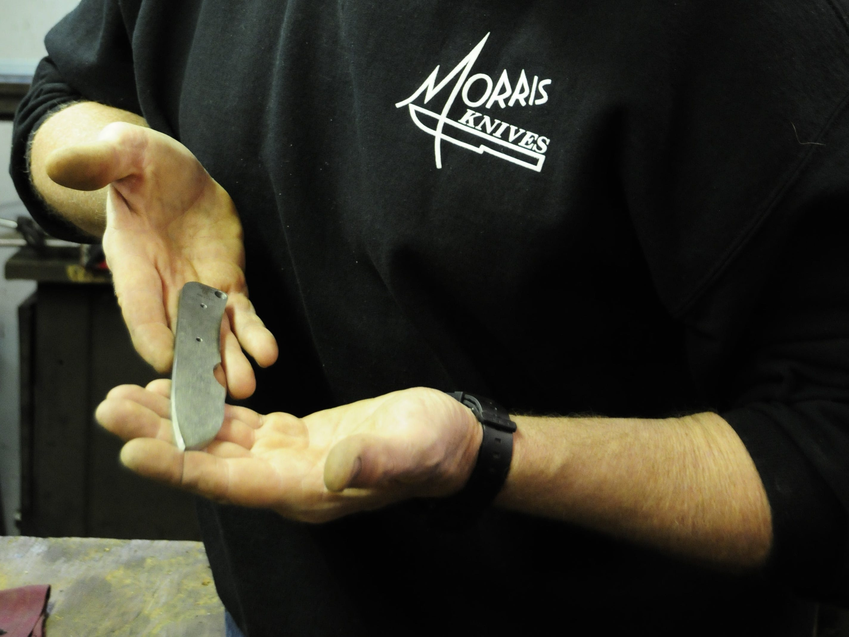 Knifemaker Michael Morris displays a blade at his shop in Yale.