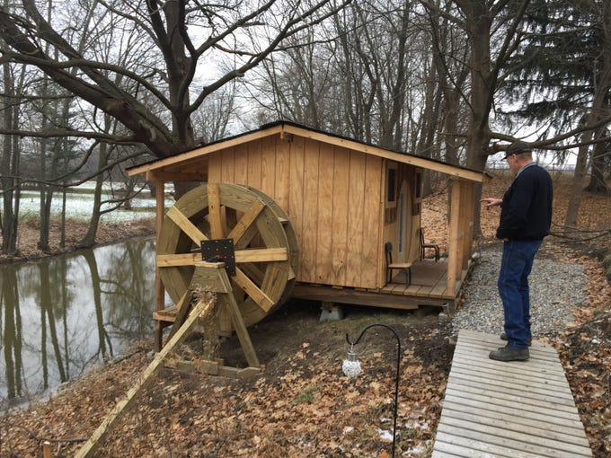 Michael Morris walks near a waterwheel built to hobbit scale at his property along Mill Creek in Yale.