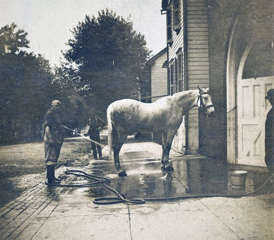 A member of the Good Will Fire Company No. 3 washing one of their fire horses in front of their fire station on East Catherine Street in the early 1900s.