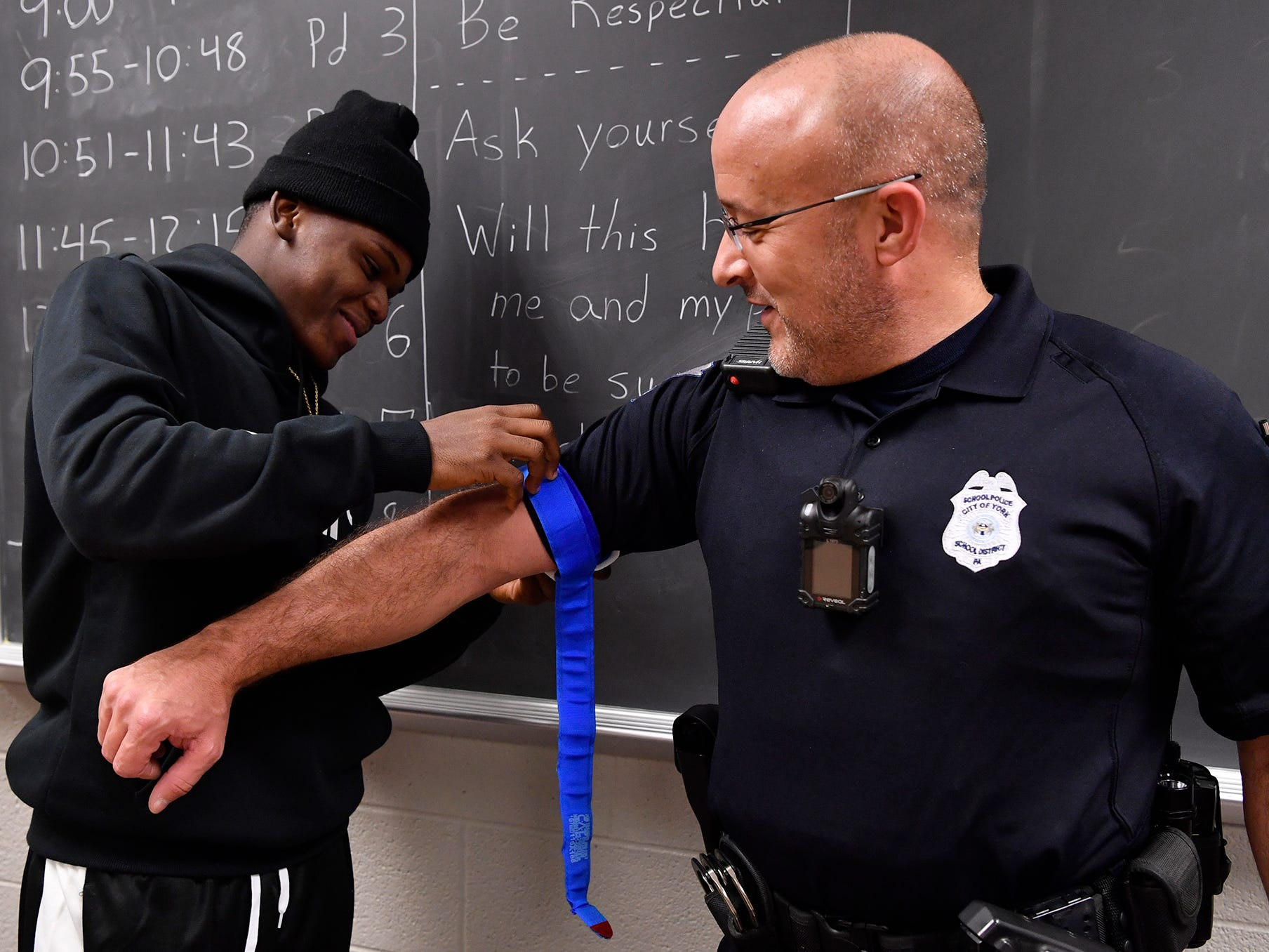 """William Penn Senior High School Public Safety and Emergency Services student Steve Prince, left, applies a tourniquet to School Police Officer Bryan Einsig during a """"stop the bleed"""" class, Tuesday, November 27, 2018. John A. Pavoncello photo"""