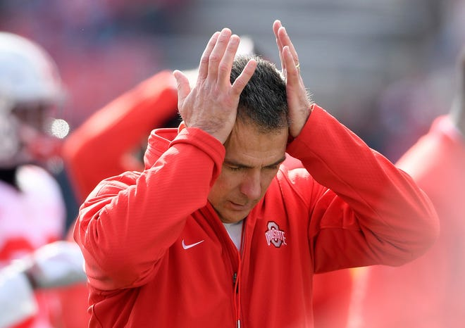 FILE - In this Nov. 17, 2018, file photo, Ohio State head coach Urban Meyer holds his hands to his head before an NCAA football game against Maryland in College Park, Md.  Urban Meyer, the highly successful football coach who won three national championships and sparked controversy and criticism this season for his handling of domestic violence allegations against a now-fired assistant, will retire after the Rose Bowl, the Ohio State University announced Tuesday, Dec. 4, 2018. Ohio State didn't immediately say why Meyer was stepping down after seven years at Ohio State and an 82-9 record, but the 54-year-old coach has previously cited health concerns. He has an arachnoid cyst in his brain that causes severe headaches. (AP Photo/Nick Wass, File)