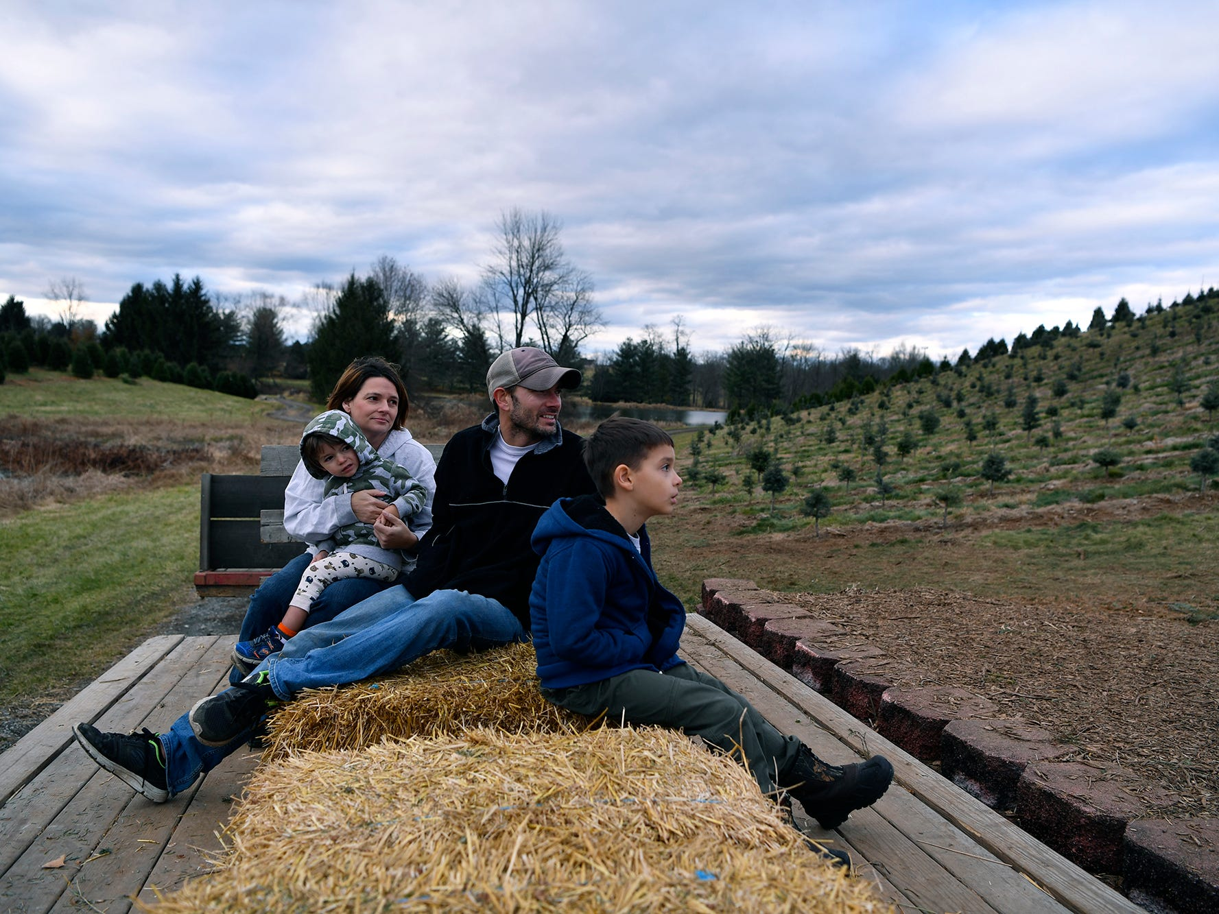Kerri and Brandon Kuykendall of Mechanicsburg, head out into McCurdy's Tree Farm in Dillsburg with their sons Tristan, 2, and River, 7, to search for the perfect Christmas tree, Monday, December 3, 2018. 