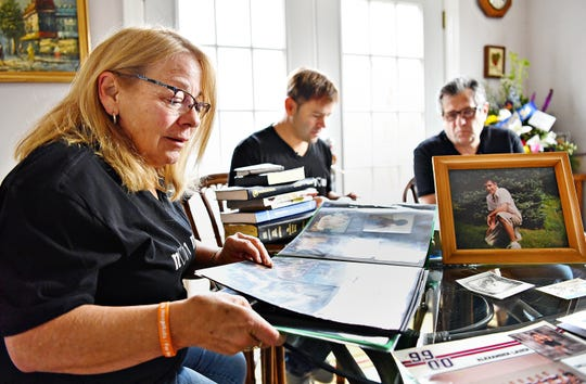 Mary Lauer, left, and her husband Donald Lauer, right, sit with their son Garret Lauer, of Orlando, Fl., at the kitchen table as they look through photo albums, journals and a plethora of notes and other research materials at their home in York Township, Tuesday, Dec. 4, 2018. The materials belonged to Garret's younger brother Alexander Lauer, 33, who lost his more than 10 year battle with heroin unexpectedly on Nov. 20., just one week after being released from York Hospital for drug treatment. Dawn J. Sagert photo