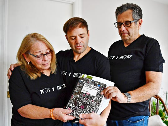Mary Lauer, left, and her husband Donald Lauer, right, stand with their son Garret Lauer, of Orlando, Fl., as they hold a notebook that belonged to Garret's younger brother, Alexander Lauer, at their home in York Township, Tuesday, Dec. 4, 2018. The notebook is just one of many vessels of notes journals and other research materials that Alexander Lauer, 33, used as he worked through his more than 10 year battle with heroin addiction. Alex lost his battle on Nov. 20., just one week after being released from York Hospital for drug treatment. Dawn J. Sagert photo