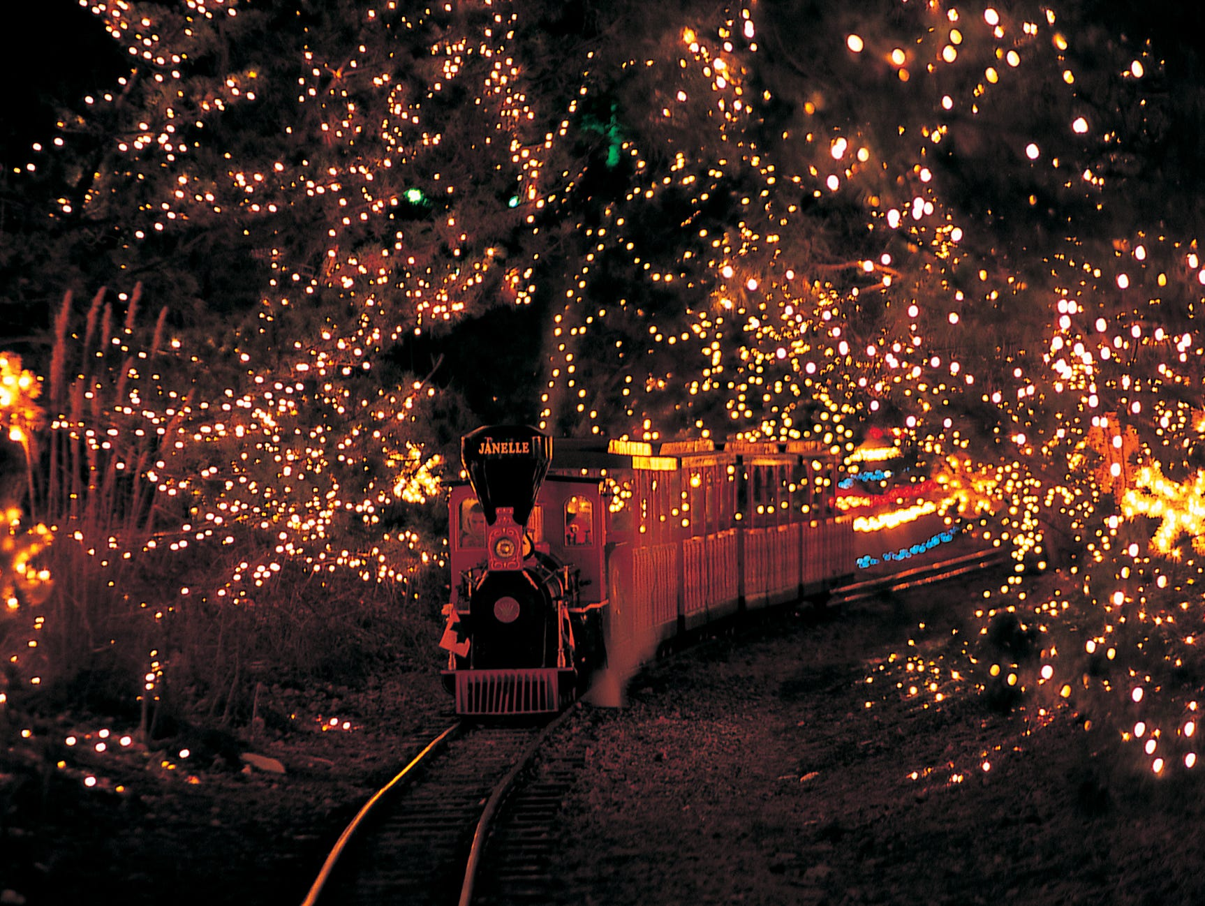 Families can take a holiday train ride through the gardens of Hersheypark.