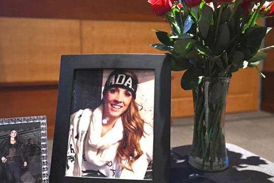 A framed photo of Haylee Ponte on a table next to a bouquet of red roses. Ponte died at 19 in 2015. She registered as an organ donor and a portrait of her will be featured in the Rose Parade in January.
