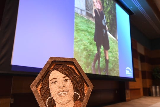 A photo of a portrait of Haylee Ponte. A photo of Haylee and her mother, Nancy Ponte, is seen in the background. The portrait, which was made from ground coffee and spices, will be featured in the Rose Parade in January.