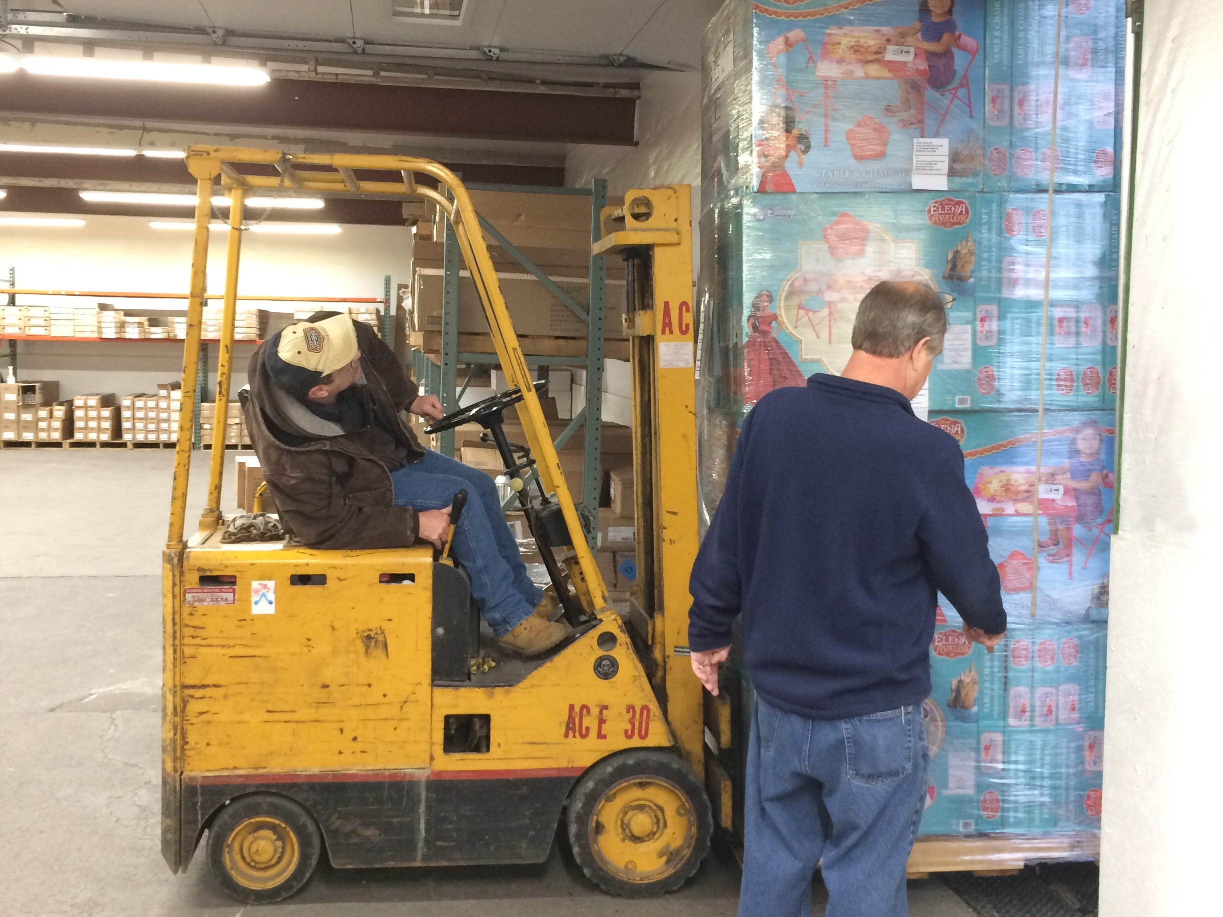 Anthony Wilmoth drives a forklift and Ron Ebacher assists as they unload toys from a semi Tuesday morning.