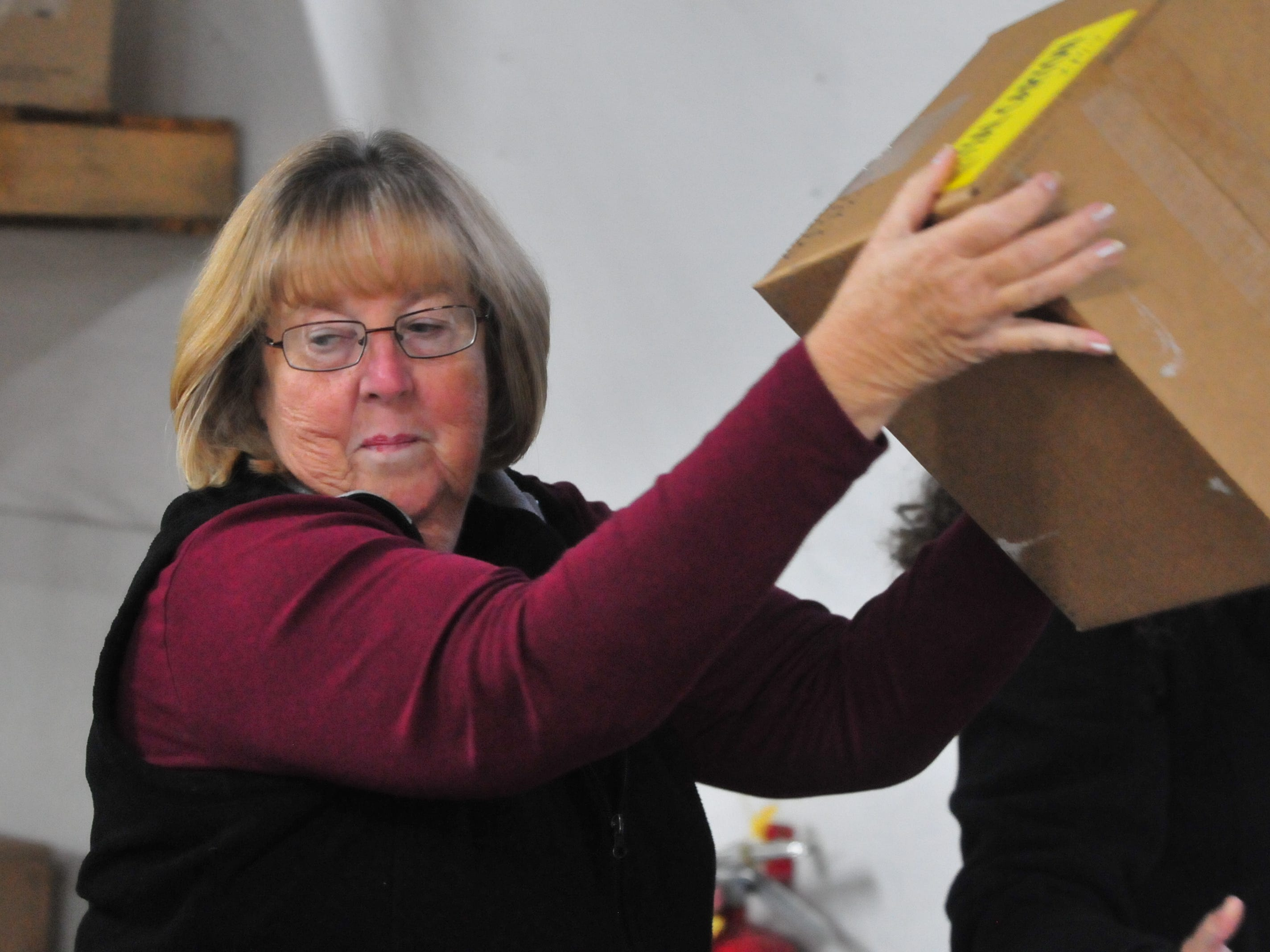 Diane Whitehead of Richmond Police Department helps break down a pallet of toys Tuesday.