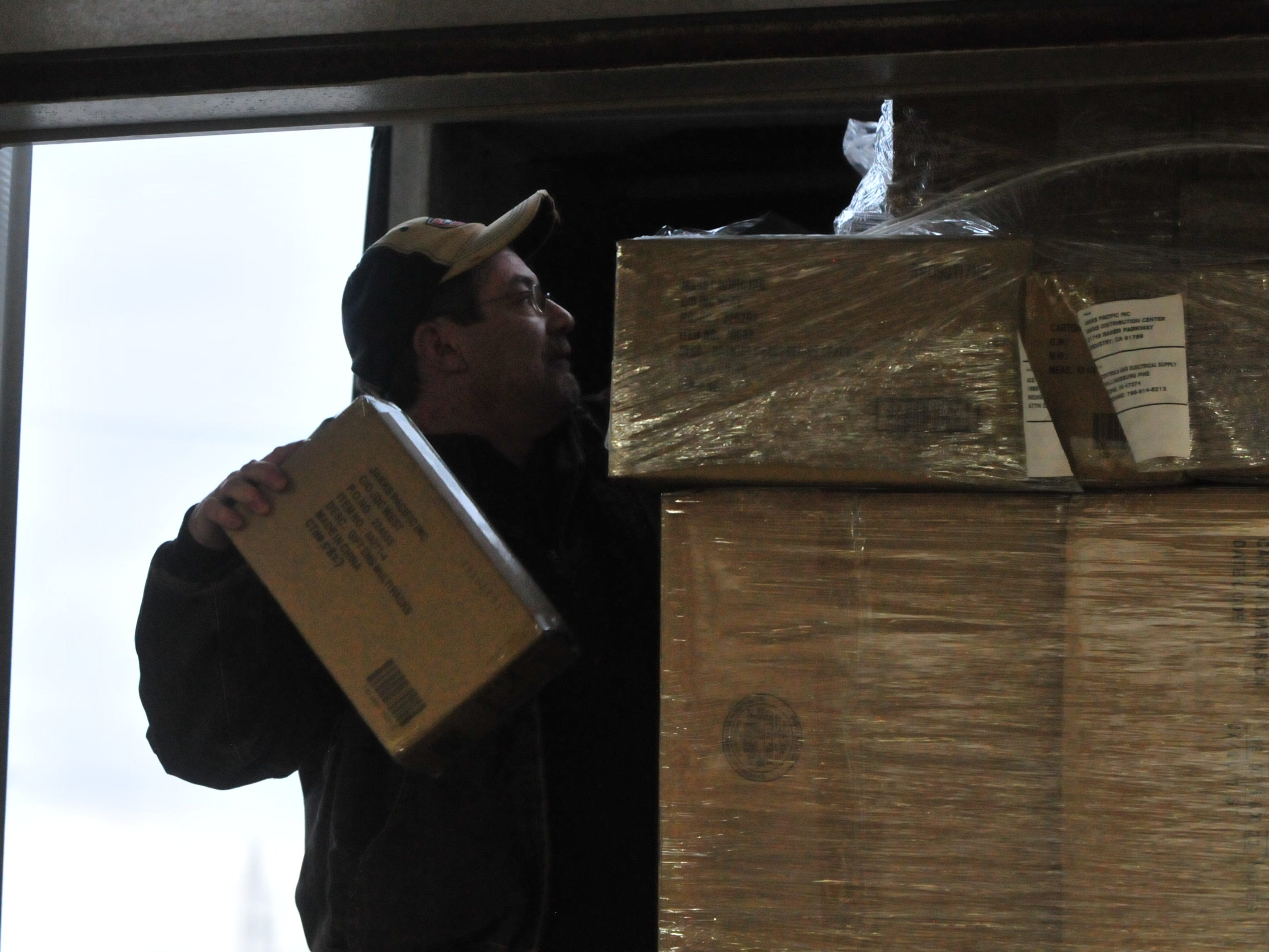 Anthony Wilmoth breaks down a pallet of toys he was unloading from a semi because it was too tall to fit through the loading dock door.