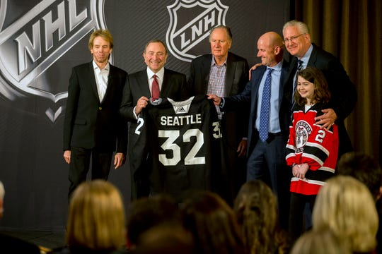 NHL commissioner Gary Bettman, center left, holds a jersey after the NHL Board of Governors announced Seattle as the league's 32nd franchise, Tuesday, Dec. 4, 2018, in Sea Island Ga.. Joining Bettman, from left to right, is Jerry Bruckheimer, David Bonderman, David Wright, Tod Leiweke and Washington Wild youth hockey player Jaina Goscinski.