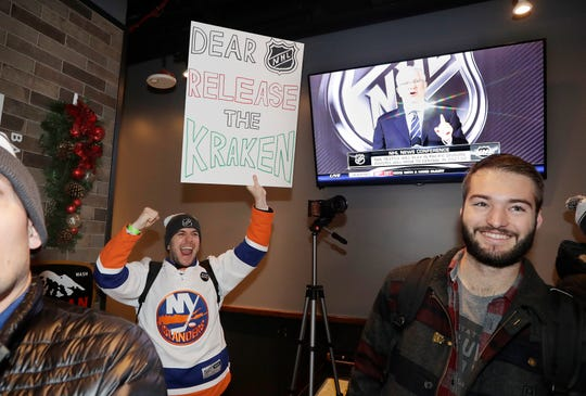 """Max Rubin cheers and holds a sign in favor of the team name """"Kraken"""" following the announcement of a new NHL hockey team in Seattle, at a celebratory party Tuesday, Dec. 4, 2018, in Seattle."""