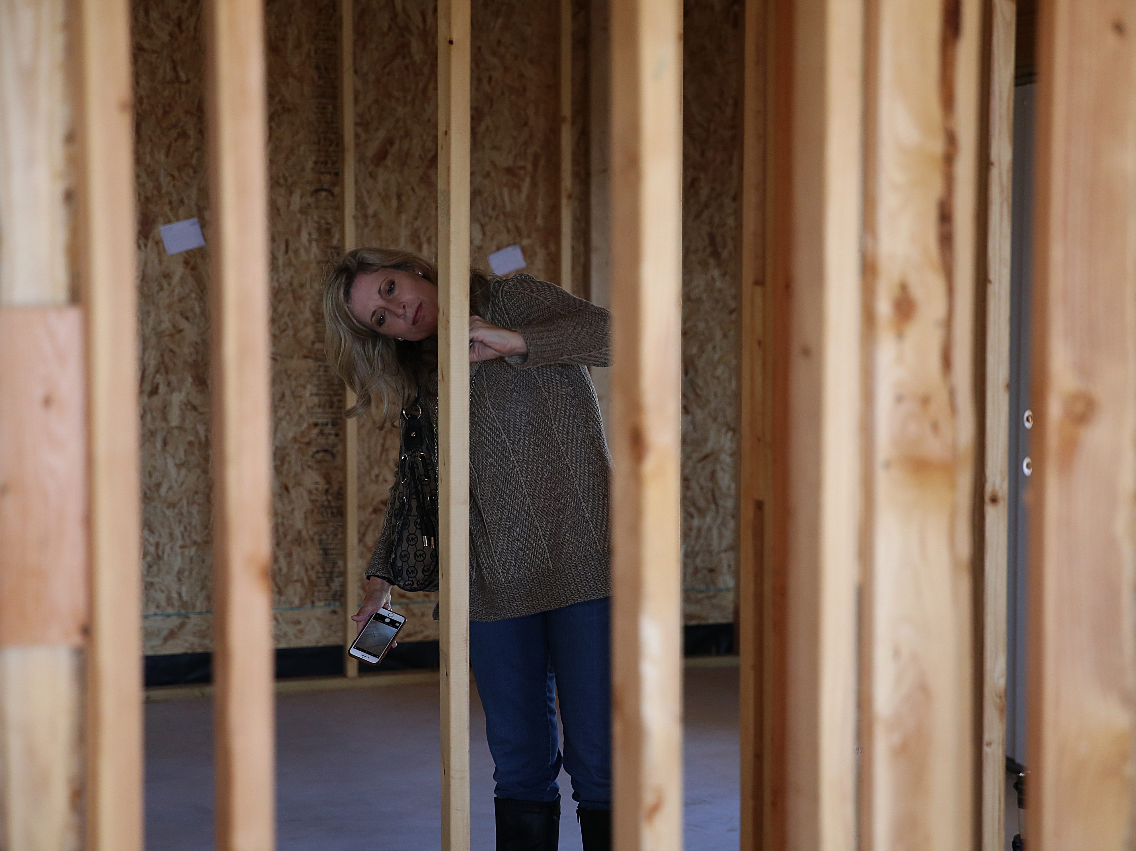 Kristen Oliver with the Home Builders Association writes a messages of support for Army Pfc. Ian Rook and his family Tuesday, Dec. 4, 2018 inside of the family's unfinished home.