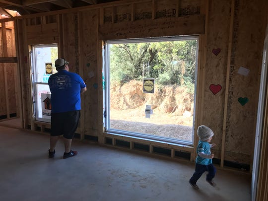 Ian Rook looks out the back window of his new home in San Angelo as his son Johan explores. The Rooks are receiving the mortgage-free home through Operation Finally Home, which provides homes to veterans.