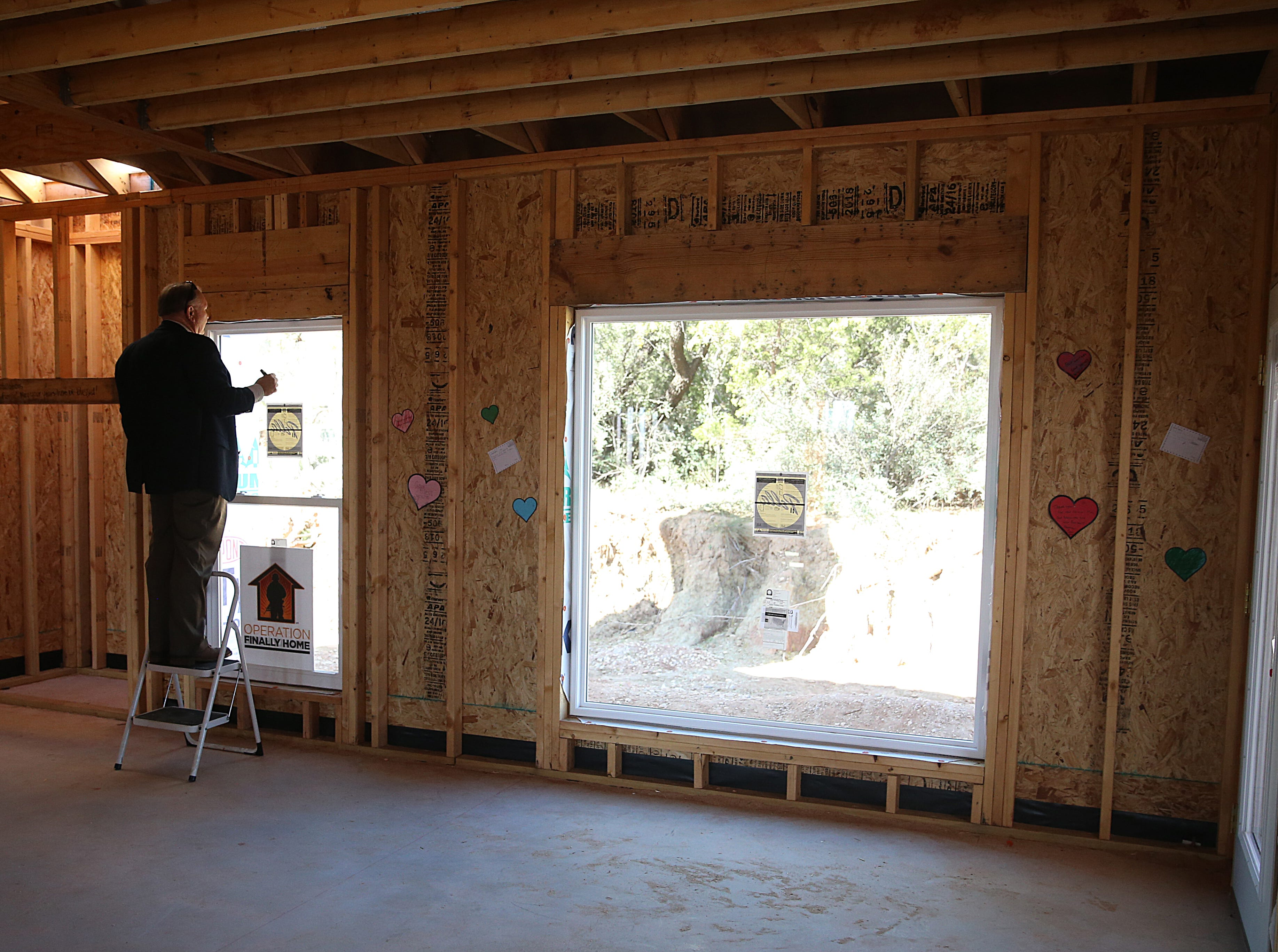 Mike Biggerstaff of Biggerstaff Homes writes a messages of support for Army Pfc. Ian Rook and his family Tuesday, Dec. 4, 2018 inside of the family's unfinished home.