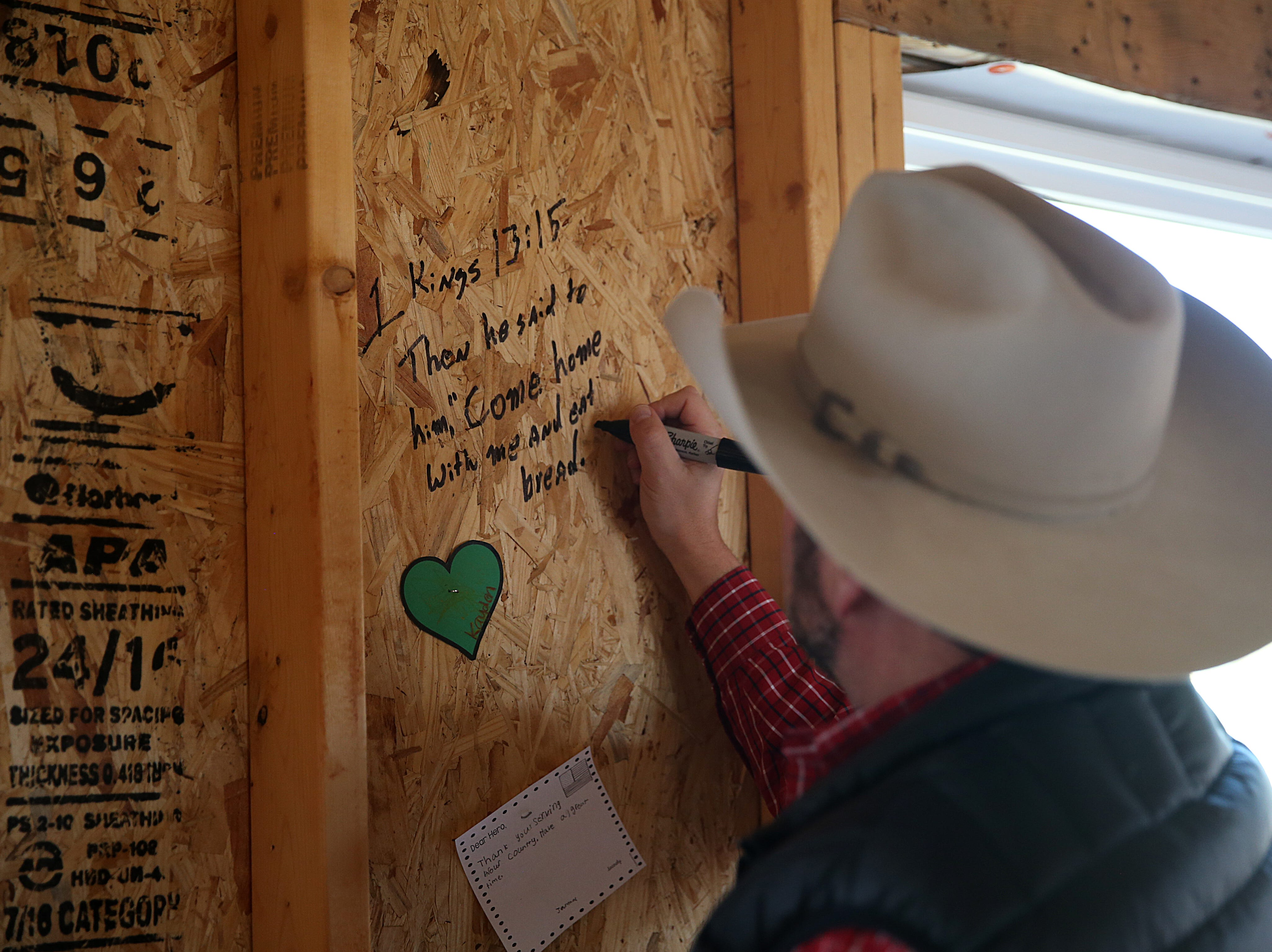 Visitors write messages of support for Army Pfc. Ian Rook and his family inside of the family's unfinished home Tuesday, Dec. 4, 2018. The Rooks received a mortgage-free home as part of Operation Finally Home.