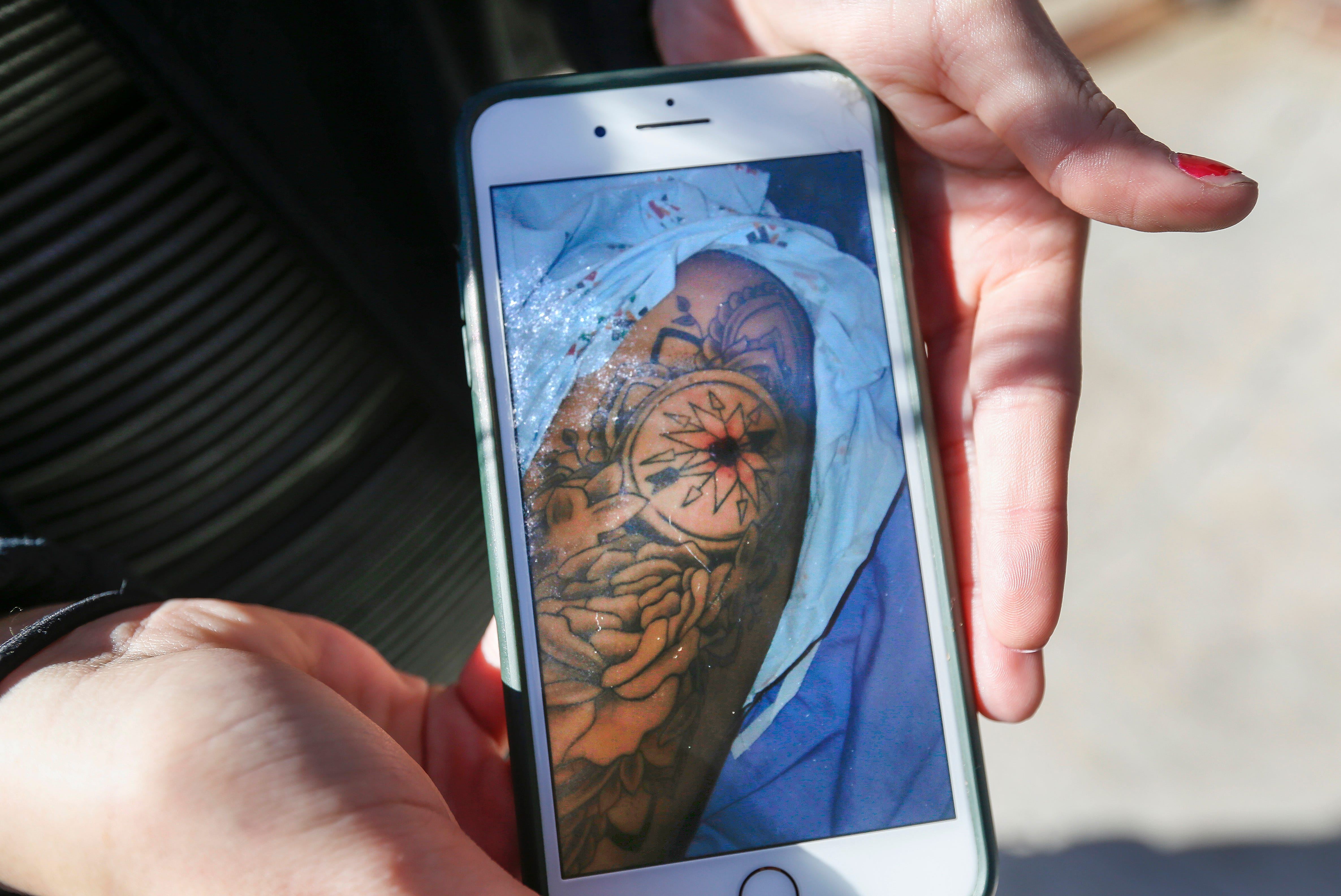 Kahlie Clark displays a photo on her cell phone of a bullet wound she sustained after being shot in the arm while spending time with friends at Tropical Liqueurs in downtown Springfield.