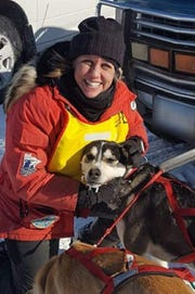 Darcy Stanley-Nord with a sled dog.
