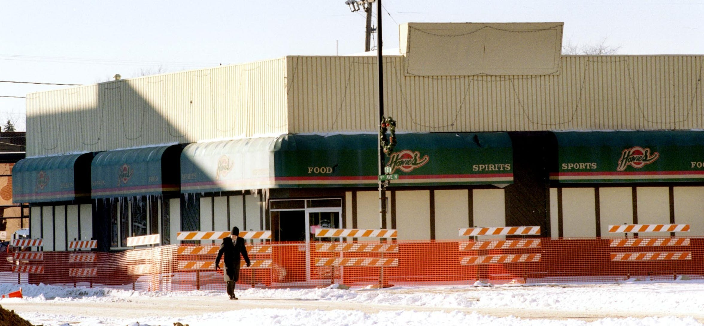 A pedestrian wandered through the barricaded area surrounding Howie's Bar on Dec. 14, 1998 in downtown St. Cloud.