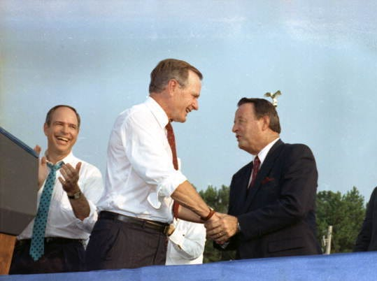 In this Sept. 6, 1990 file photo, former president George H.W. Bush shakes hands with former Florida State head football coach Bobby Bowden while campaigning for the re-election of Congressman Bill Grant.