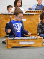 Kindergartners Joseph Marschka (front) and Lyla Roberts (behind) play xylophones.